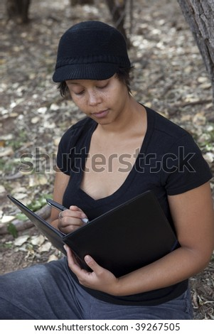 Young african-american woman sitting in forest, studying her notes - stock photo