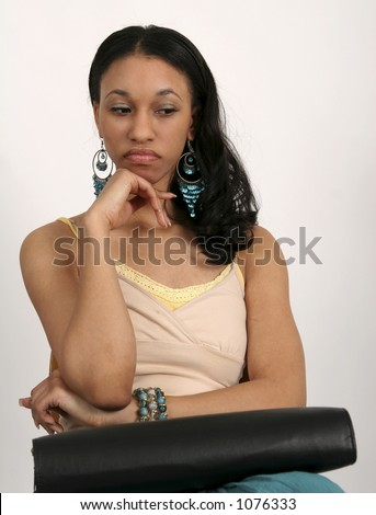 Young African American woman sitting with portfolio in her lap - stock photo