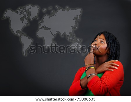 young African American woman thinking and looking at the world map with a positive attitude. - stock photo
