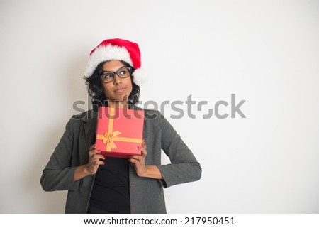 Young African American woman wearing a santa hat opening a gift box, isolated on white background - stock photo