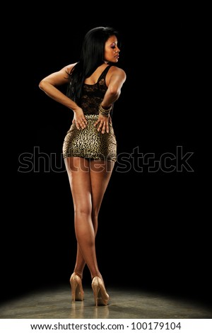 Young African American Woman wearing high heels and a mini skirt on a dark background