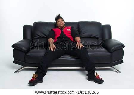 Young African American Woman with a Mohawk Haircut on a Black Leather Couch
