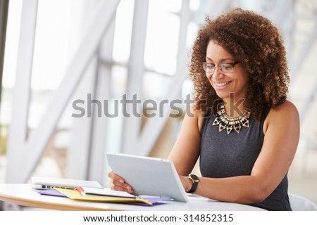 Young African American woman working with tablet in office - stock photo