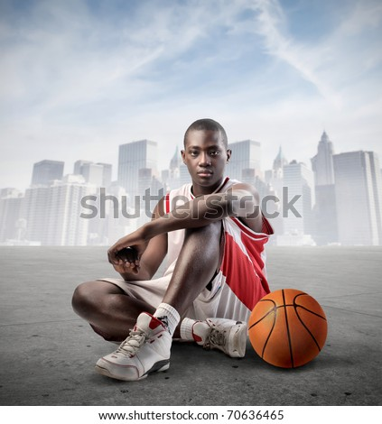 Young african basketball player with cityscape on the background