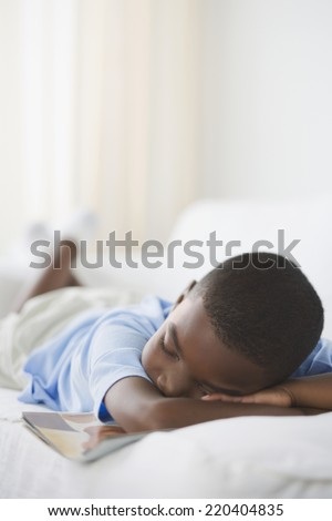 Young African boy sleeping with book on sofa - stock photo