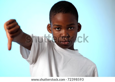 Young african boy thumbs down sign on horizontal color background - stock photo