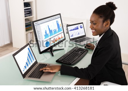 Young African Businesswoman Analyzing Graph On Computer - stock photo