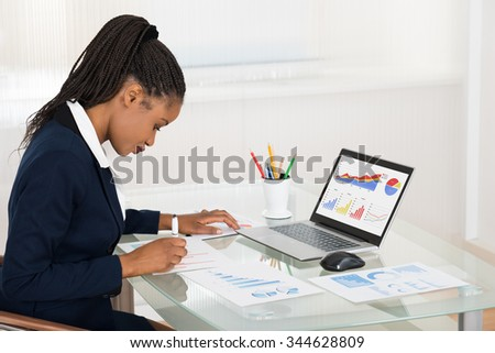 Young African Businesswoman Analyzing Graph While Laptop On Office Desk - stock photo