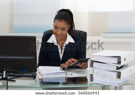 Young African Businesswoman Calculating Bills Using Calculator - stock photo