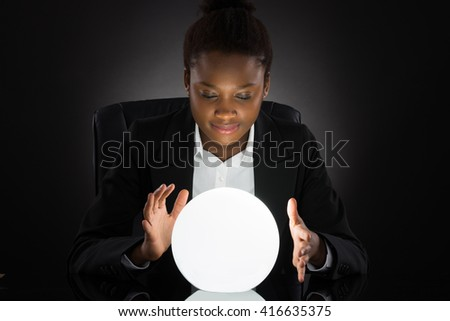 Young African Businesswoman Predicting Future With Crystal Ball On Desk Over Black Background - stock photo