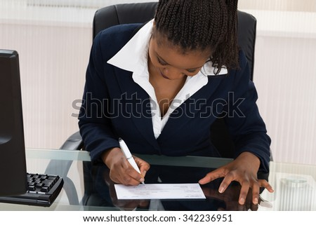 Young African Businesswoman Signing Cheque At Office Desk - stock photo