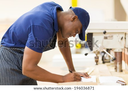 young african carpenter working in workshop - stock photo