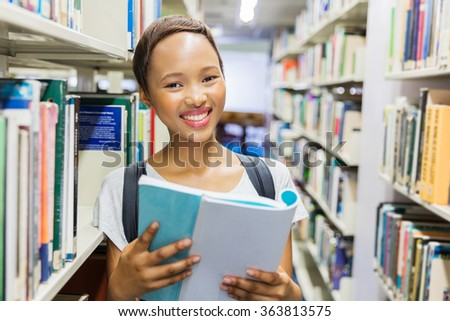 young african college student reading a book in library - stock photo