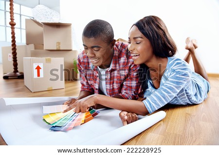 young african couple having fun deciding on paint colour swatch for new home apartment - stock photo