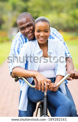 young african couple riding bicycle