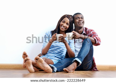 Young african couple sitting on floor of new home with coffee and being happy with life success of property investment - stock photo