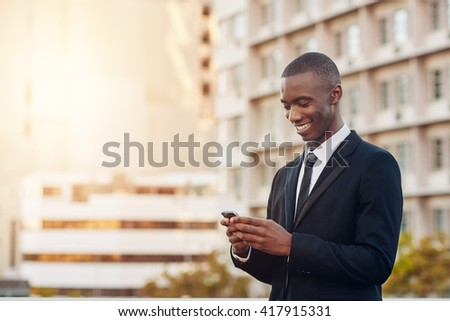 Young African entrepreneur smiling at his phone in a city - stock photo