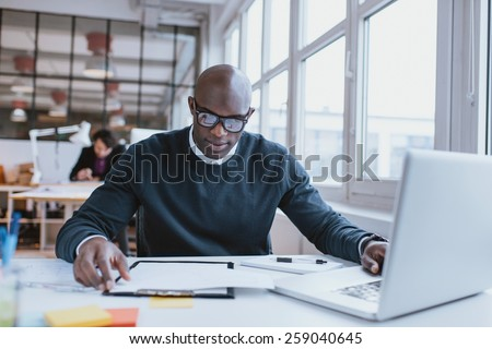 Young african executive sitting at his desk with laptop reading a document. African man working in office. - stock photo