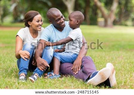 young african family of three sitting together outdoors - stock photo