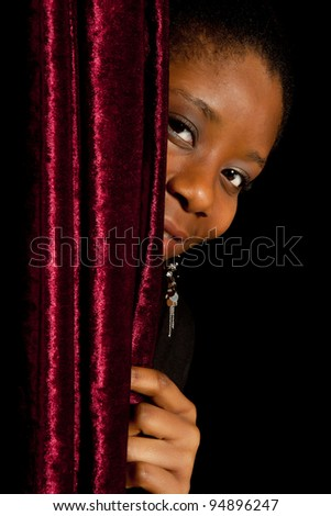 Young African Ghanese woman hiding shy behind a curtain - stock photo