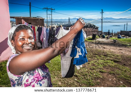 young african girl hanging her family's laundry to dry in the township - stock photo