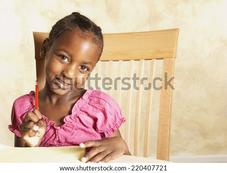 Young African girl holding pencil and smiling - stock photo