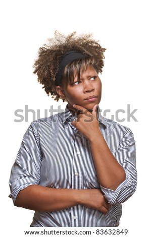 Young African girl looks off camera with a skeptical expression in front of white. - stock photo