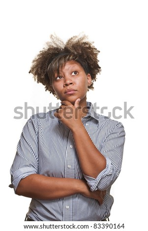 Young African girl poses in front of a white background with a thoughtful look. - stock photo