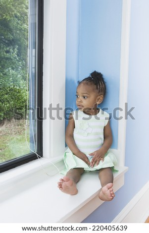 Young African girl sitting in window seat - stock photo
