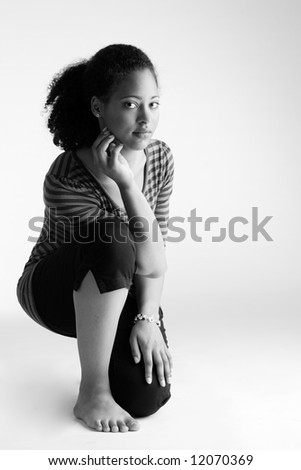 Young african girl sitting on her knee and looking into the lens