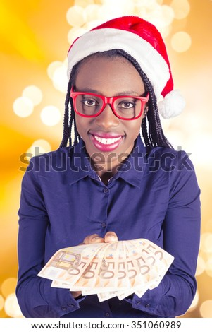 Young African girl with Christmas hat and money  - stock photo