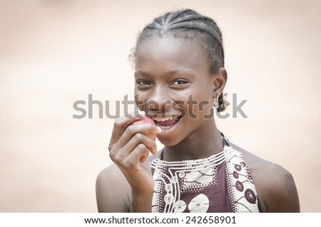 Young African Gorgeous School Girl Biting Into An Apple Whilst Smiling Positively - stock photo