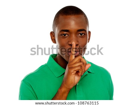 Young african guy showing silence gesture with finger on his lips
