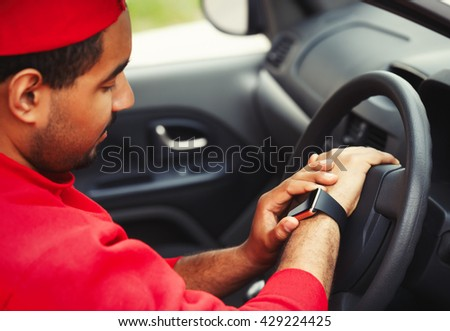 Young african guy using trendy smart wrist watches sitting in a car. Popular new technology to always stay connected to internet and social media. Close up macro