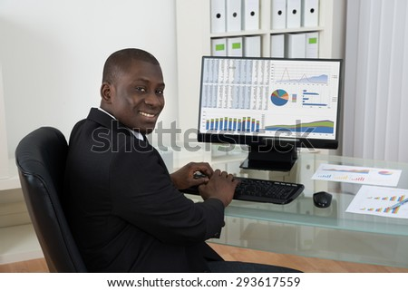 Young African Happy Businessman Working On Computer At Desk In Office - stock photo