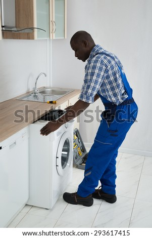 Young African Male Technician Pulling Washing Machine In Kitchen - stock photo