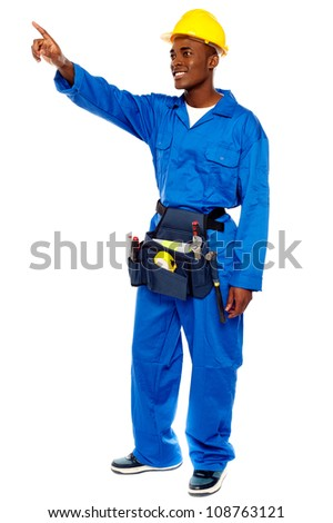 Young african male worker pointing at copy space, full length portrait