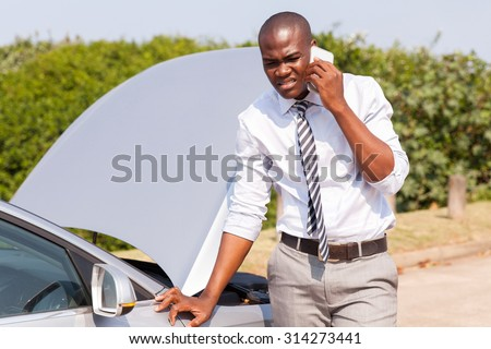 young African man calling for assistance with his car broken down by the roadside - stock photo