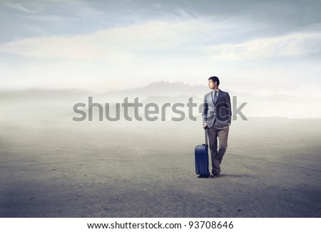 Young african man holding a suitcase in a desert - stock photo