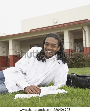 Young African man smiling on school campus - stock photo