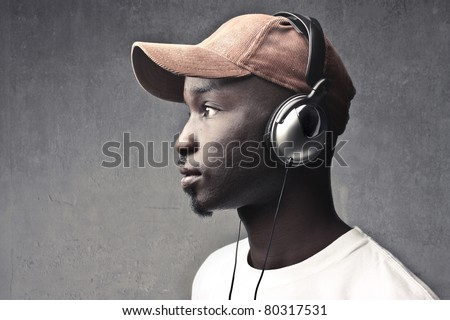 Young african man wearing a cap and headphones - stock photo