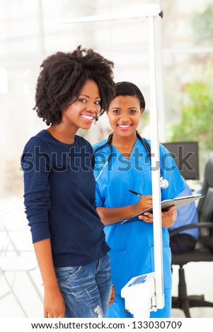 young african nurse measuring patient's height and weight on scale - stock photo