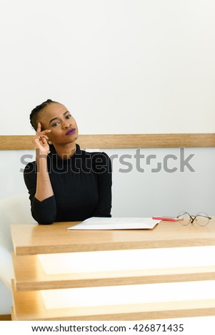 Young African or black American woman holding hand near face thinking and looking away at desk in office - stock photo