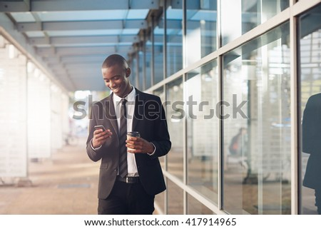 Young African professional man smiling at his phone outdoors - stock photo