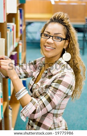 young african student in library searching for books - stock photo