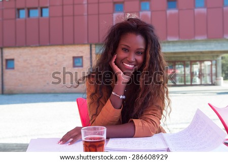 Young african student preparing her exams at a local cafeteria - stock photo