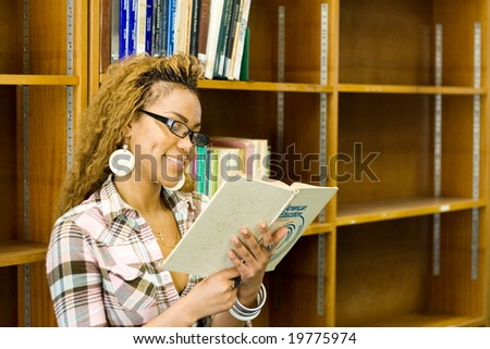 young african student reading in library - stock photo