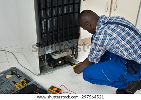 Young African Technician Fixing Refrigerator With Worktool - stock photo
