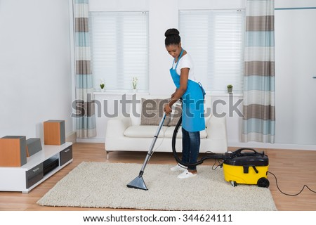 Young African Woman Cleaning Carpet With Vacuum Cleaner - stock photo