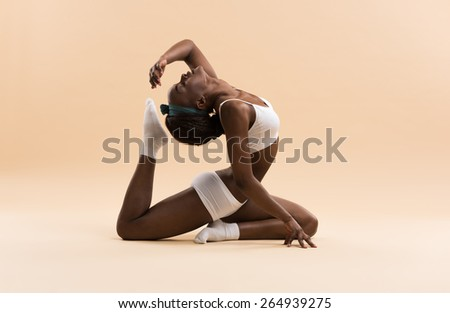 Young African woman doing yoga in stretching position - stock photo